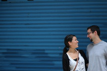 a couple talking in front of a blue wall
