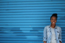 an African American woman standing in front of a blue wall
