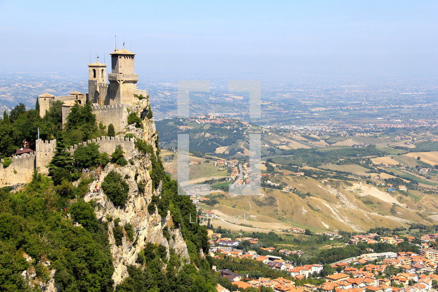 a castle on a mountainside over a valley village