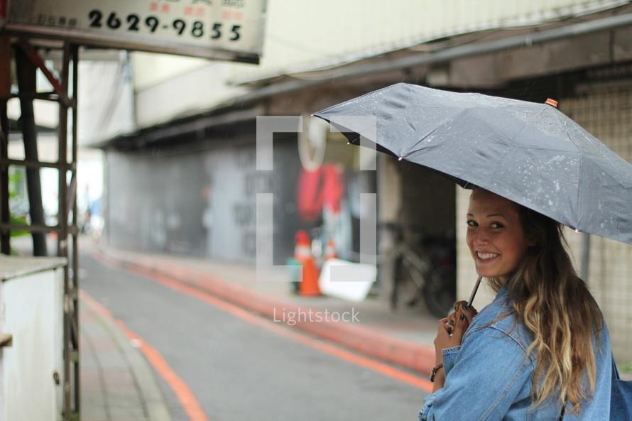 a woman walking down the street carrying an umbrella