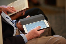 man sitting at a Bible study reading a tablet