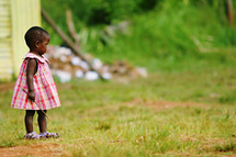 toddler african black girl holding a stick in a dress