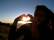 teen girl making a heart with her hands