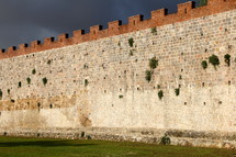 fortress wall and green grass with dark storm clouds behind