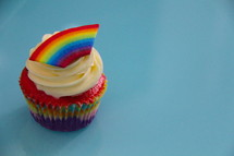 Cupcake decorated with cream cheese and a fondant rainbow