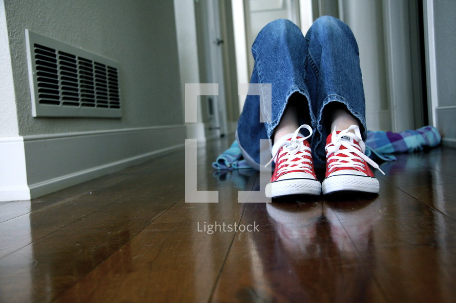 teen boy lying on a wood floor