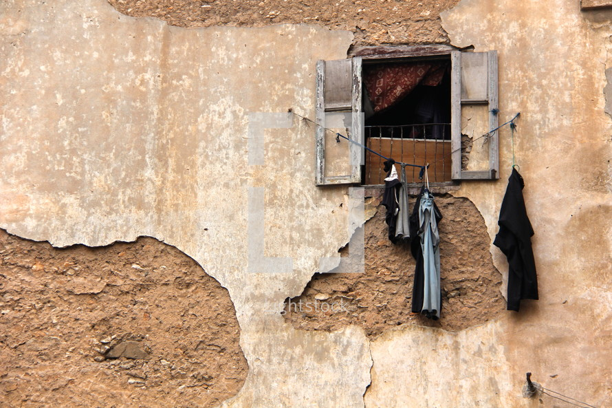 Clothes hanging on a line outside the window of a weathered adobe building.