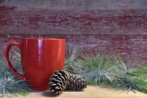 red mug, pine cones, and Christmas greenery