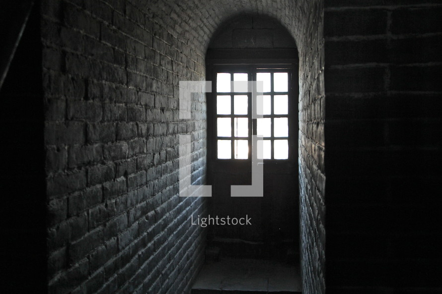 Sunlight shining through a window into a dark brick room