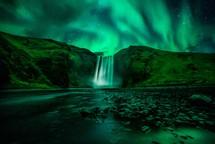 green aurora and waterfall