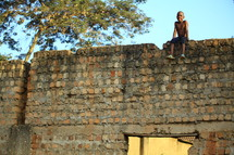 boy child sitting on a brick wall