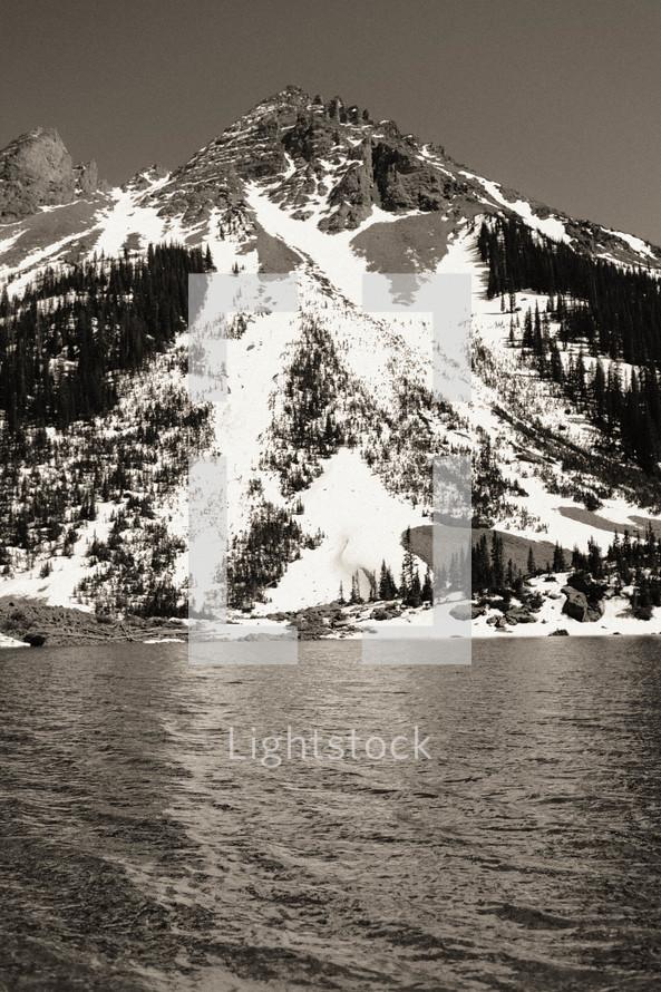 snow on a mountainside along a shore