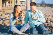a couple on their honeymoon on a beach having a picnic