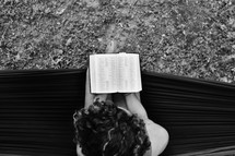 a woman on a hammock reading a Bible