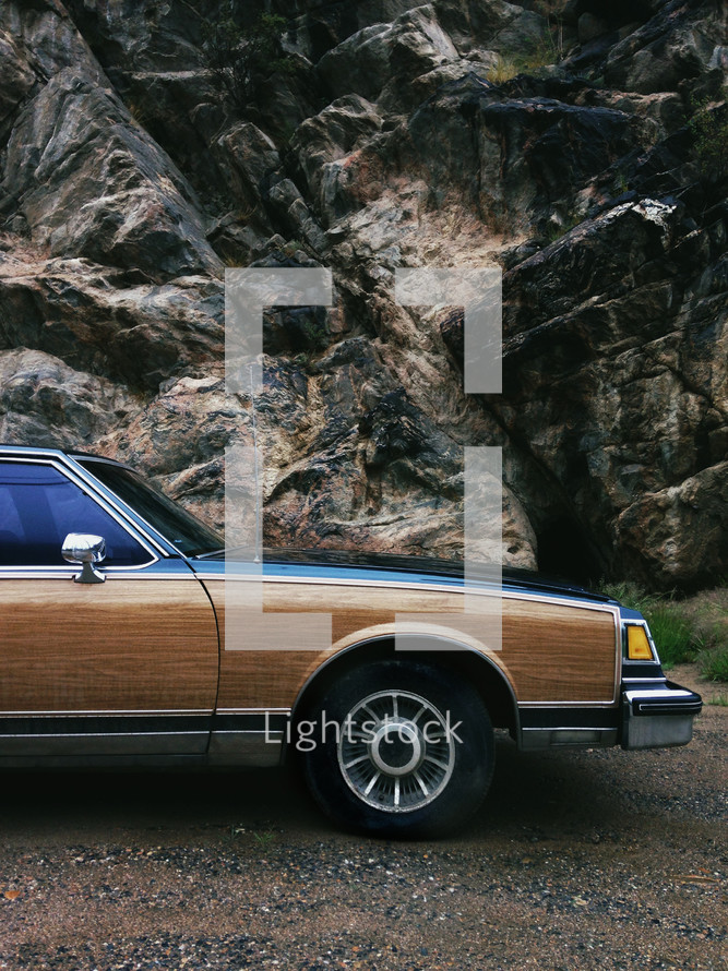 old station wagon and rock cliff
