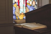 open Bible on the pulpit and stained glass window