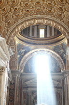 Sun streams through a window in St. Peter's Basilica, Vatican City