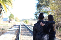 sisters standing on railroad tracks