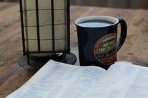 lantern, Bible, and coffee mug on a picnic table at camp