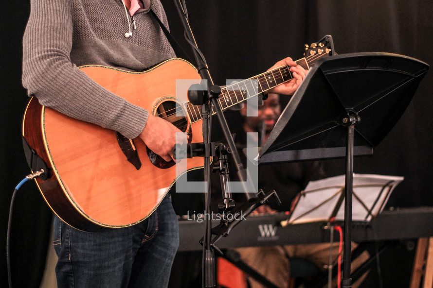 a man standing on stage playing an acoustic guitar