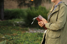 a young woman holding a Bible outdoors