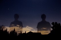 Two towering shadows of men in the night sky.