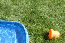 plastic swimming pool and bucket in grass