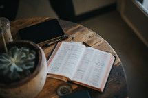 open Bible, tablet, pen, and plant on a table