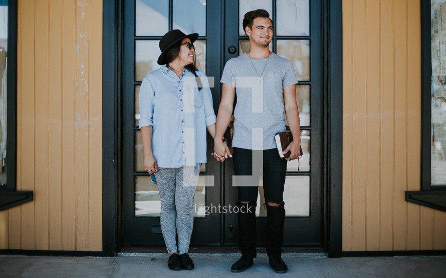 a couple holding hands and holding a Bible
