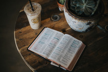 open Bible and iced coffee on a table