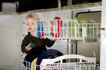 a toddler boy loading a dishwasher