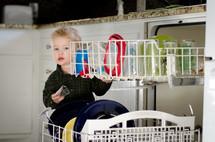 a toddler boy loading a dishwasher
