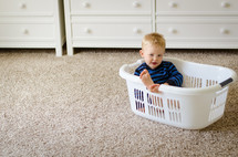 a toddler boy sitting in a laundry basket