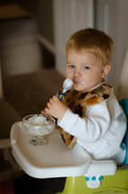 a toddler boy eating yogurt in a highchair