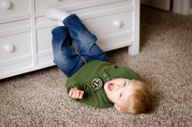 a toddler boy rolling on the floor