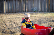 a happy toddler boy in a red wagon