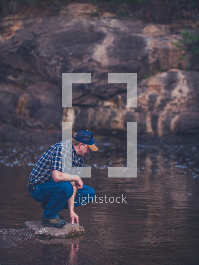 a man on a rock by a river shore