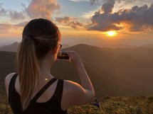 a woman taking a picture of the setting sun
