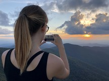 a woman taking a picture of the rising sun