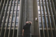a man standing between buildings looking up