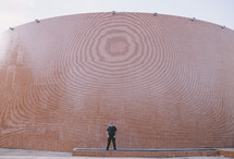 a man standing in front of a curved brick wall