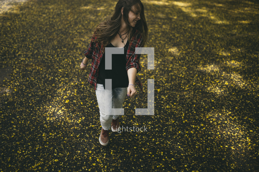 teen girl walking through a field of yellow wildflowers