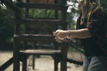 a teen girl swinging on a swing