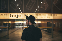 man in a black hat standing in front of a cinema marque