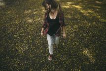 teen girl walking through a field of wildflowers
