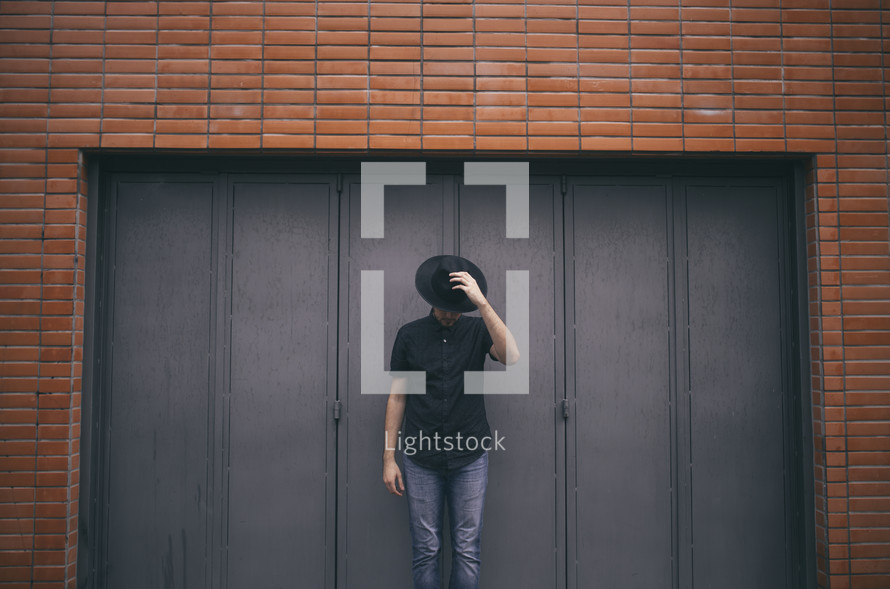 man standing in front of a brick warehouse building