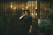 A woman in a hat standing by a metal gate.