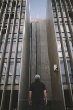 a man standing between two buildings looking up