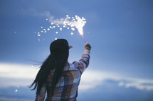 A woman holds a fiery sparkler against the evening sky.