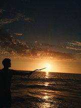 a man with a stick standing on a beach at sunset